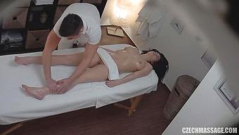 Массажист массирует тело обнаженной клиентки