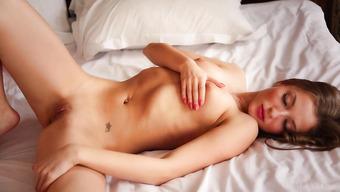 Хрупкая брюнетка лежит на кровати без одежды
