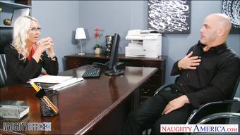 В офисе блондинка с большими сиськами стоит раком перед парнем